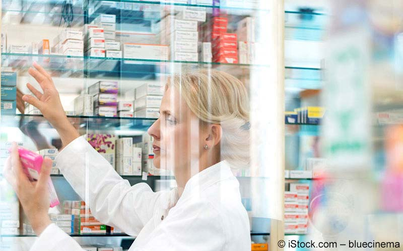 Apothekerin schaut auf ein Medikament